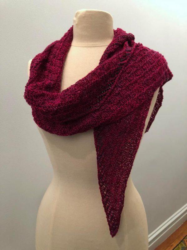 a shawlette with raspberry yarn with black diamond beads